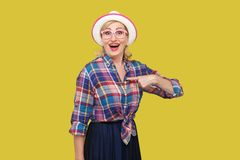 Who? me? Portrait of surprised modern mature woman in casual style with hat and eyeglasses standing, looking with amazed face,. Pointing herself and asking royalty free stock images