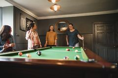 Who is Next. Small group of female friends playing a game of pool in a games room in a house royalty free stock images