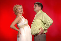 Who's belly larger?. Kind of joke: who's belly is larger - pregnant woman's or her husband's? Young couple on red background. Horizontal version royalty free stock photography