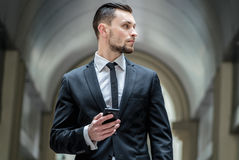 Who's calling? Young businessman holding a mobile phone looking. Side Stock Image