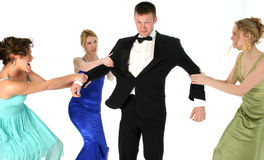 Who's Man Is He?. Three beautiful young woman in formal dresses fighting over handsome man in tuxedo. Shot in studio over white Royalty Free Stock Image
