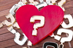 Who's my Valentine?. Red plexiglas heart with a gold question mark on it lies on a wooden background with many other question marks royalty free stock photos