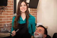 Who's ready for a shave?. Gorgeous female barber holding a razor and about to shave a men in a barber shop Stock Image