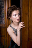 Who's There??. Beautiful young brunette woman dressed in an elegant evening gown looking nervously around a door royalty free stock photos