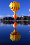 Who's on top. Hot air balloon floating over lake with balloon reflections royalty free stock image