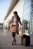 Who should I call. Woman who arrived to the airport and looks her phone Royalty Free Stock Photo