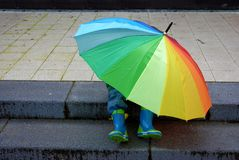 Who is under the umbrella, boy or girl?. Who sits hidden under a giant rainbow-colored umbrella, boy or girl stock photos