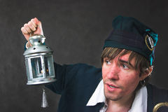 Who is there?. Man with lamp on the dark background Royalty Free Stock Photos