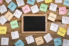 Who, why, what, when, how, where and question marks on crumpled adhesive notes. Around a small blank blackboard on a wooden background stock photos