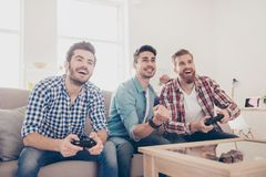 Who will win? Competition of guys playing car race. Excited friends are playing games indoors at home, sitting on cozy beige royalty free stock image