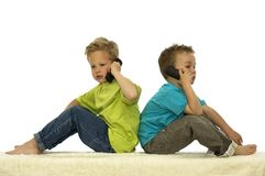 Who Are You Calling. Two friends calling someone on the phone while sitting with their backs against each other royalty free stock images