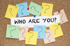 WHO ARE YOU?. WHO ARE YOU text in the middle of question marks pinned on cork bulletin board Stock Photo