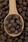 Whole allspice berries in a wooden spoon. Whole allspice berries background with a wooden spoon on top stock photo