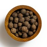 Whole allspice in dark wood bowl isolated on white. Whole allspice in dark wood bowl isolated on white from above stock photography