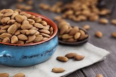 Bowl of Almonds. Whole almonds in bowl and wooden spoon against a rustic background Royalty Free Stock Photos