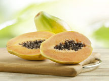 Whole And Halved Papayas On A Wooden Board Royalty Free Stock Photography