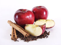 Whole Apple, Sections, and Spices, profile. A red whole apple with two quartered sections on cloves and cinnamon sticks.  On white Stock Photos