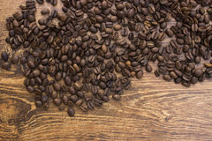 Whole aromatic coffee beans on a wooden background closeup. Royalty Free Stock Photos