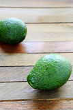 Whole avocado on wooden surface stock images