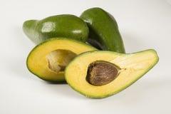 Whole avocados and a avocado cut in a half. Stock Photo