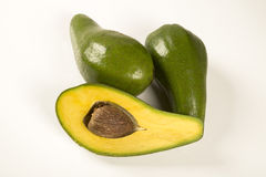 Whole avocados and a avocado cut in a half. Stock Image