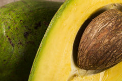 Whole avocados and a avocado cut in a half. Royalty Free Stock Images