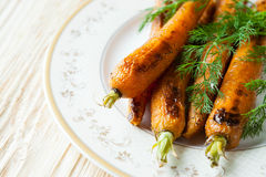 Whole baked carrots on a plate Stock Images