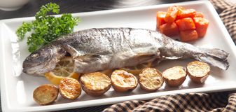 Whole Baked Rainbow Trout on a Table Set for Dinner. A Whole Baked Rainbow Trout on a Table Set for Dinner stock photos