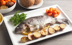 Whole Baked Rainbow Trout on a Table Set for Dinner. A Whole Baked Rainbow Trout on a Table Set for Dinner stock image