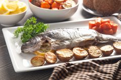 Whole Baked Rainbow Trout on a Table Set for Dinner. A Whole Baked Rainbow Trout on a Table Set for Dinner stock images