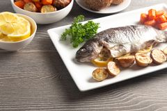 Whole Baked Rainbow Trout on a Table Set for Dinner. A Whole Baked Rainbow Trout on a Table Set for Dinner royalty free stock image