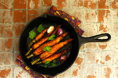 Whole baked young carrots with garlic and rosemary Royalty Free Stock Images