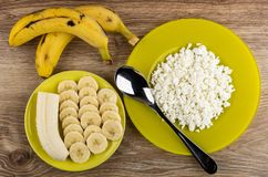 Whole bananas, yellow plate with grainy cottage cheese, spoon, slices of banana on saucer on table. Top view stock photos