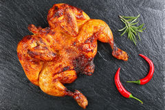 Whole barbecued golden crispy skin chicken. Flattened out whole barbecued golden crispy skin chicken tabaka on black slate tray with chili pepper and rosemary royalty free stock photography