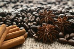 Whole bean coffee with star aniseas and cinnamon sticks on light burlap royalty free stock photography