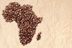 Free Whole Bean Coffee. The Contour Of The Mainland Of Africa Is Made Of Coffee Beans On Old Crumpled Paper Stock Images - 155733984