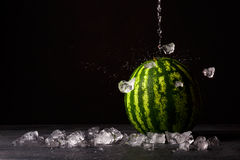 A whole big watermelon on a black table background. Green watermelon and crushed ice. Cold and sweet summer snacks. Copy stock image