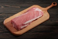 Whole boneless pork loin without fat. Pork tenderloin on a cutting board on a dark background Royalty Free Stock Images