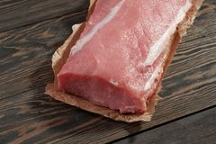 Whole boneless pork loin without fat. Pork tenderloin on paper on a dark background Stock Images