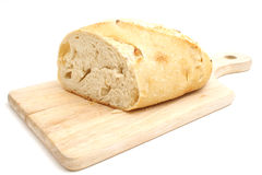 Whole bread on a cutting board. Isolated photo of whole bread on a cutting board on white Royalty Free Stock Photography