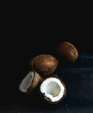 Whole and broken coconuts over dark grunge background Stock Image