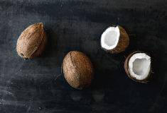 Whole and broken coconuts over dark grunge background Royalty Free Stock Photography