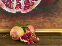 Whole and broken pomegranate on wood. Photo of whole and pieces of ripe pomegranate on wood table royalty free stock photo