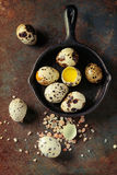 Whole and broken quail eggs. With yolk in shell and pink sea salt crystal in small iron cast pan over old rusty texture metal background. Top view with space royalty free stock images
