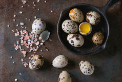 Whole and broken quail eggs. With yolk in shell and pink sea salt crystal in small iron cast pan over old rusty texture metal background. Top view with space royalty free stock photos