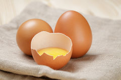 Whole and broken raw brown eggs closeup on wood Royalty Free Stock Images