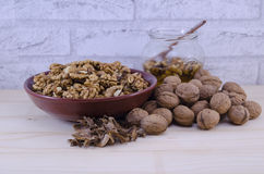 Whole and broken walnuts and a jar of honey Stock Photography