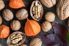 Whole and broken walnuts, physalis and autumn leaves on a wooden. Whole and broken walnuts, Physalis alkekengi Chinese lantern and autumn leaves on a wooden Royalty Free Stock Photography