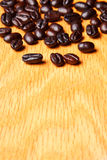 Whole brown coffee beans on wood Royalty Free Stock Photo