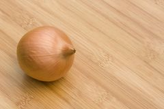 Whole brown onion on wooden table Royalty Free Stock Images